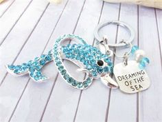 This is a sparkling rhinestone dolphin keychain that will make a pretty gift for under 20.00. A nautical keychain with a quote that reads dreaming of the sea and 2 turquoise faceted beads along with a white pearl added for extra ocean inspiration. This can also be used as a purse charm, or backpack charm for the hard to buy for teen. A practical and pretty gift. A perfect gift for the beach lover. Dolphin measures 2.5 inches long x 1.5 at its widest.