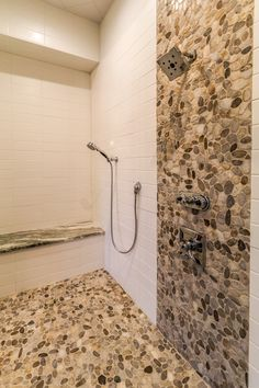 Large full size walk-in shower with custom subway tile and pebble stone detail
