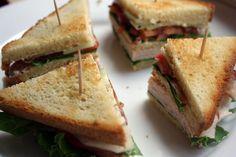 Clubsandwiches zijn altijd goed; je vindt ze dan ook op menig lunchkaart. Deze variant met kip en komkommer is iets gezonder dan de standaard Clubsandwich. Hak de peterselie en meng voor de saus de aangegeven ingrediënten met elkaar en breng op smaak met zout en peper. Toast het brood goudbruin en snijd er de korstjes …