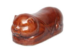 A headrest in the shape of a cat China, 19th cent. (Qing-dynasty 1644-1911). Ceramic with red-brown glaze. Oval hollow body in the shape of a sleeping cat. Hutched centre for resting the neck. Filling hole on the upper side. Manufactory mark (blind embossing).