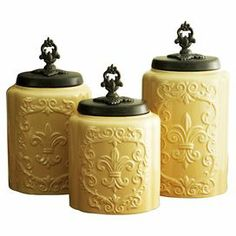 """Perfect for storing baking essentials in the kitchen or office supplies in the den, this set of earthenware canisters features an embossed fleur-de-lis motif and finial lids.   Product: Small, medium and large canisterConstruction Material: EarthenwareColor: Cream antiqueDimensions: 6"""" H x 6"""" Diameter (small)"""
