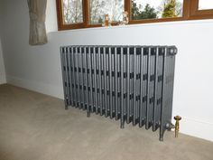 Carron Cast Iron Radiators sprayed in a Foundry grey finish and showing the radiator sitting nicely on the carpet.
