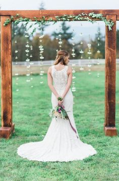 rustic wooden arch with foliage and hanging white flowers