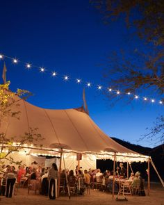 A view of the reception tent lit up at night. Tents by Zephyr Tents and lighting by Creative Lighting.