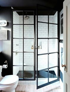 Manhattan apartment bathroom with black walls, white subway tiles and industrial style steel framed shower
