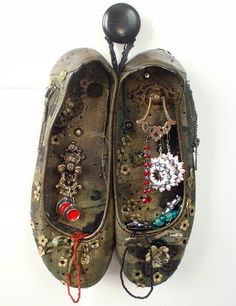Old shoes decorated, sewn together and hung on the wall for storing jewelry or displaying unusual items.