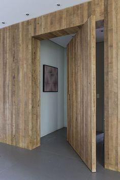 casa em itu | projeto: triplex arquitetura | painel de madeira no hall de entrada, feito de réguas de madeira peroba clara rústica. a porta pivotante leva aos quartos de hóspedes, dando mais privacidade para esta área