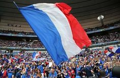 Supporters wave a large French flag as the atmosphere builds before the match.