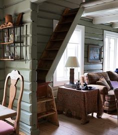 The old farmhouse was originally two separate rooms downstairs, but a wide opening has been cut in the wooden wall to link the kitchen with the living room, both of which are painted 'Lichen.' A ladder staircase on the left leads up to an open mezzanine under the pitch of the roof, now used as a bedroom for visiting grandchildren.   - CountryLiving.com