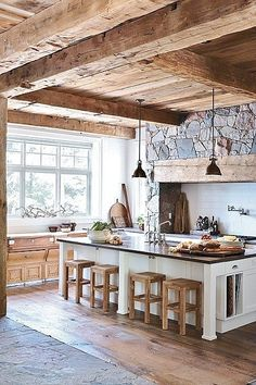 Rough hewn ceiling, antique buffet under bank of windows...absence of upper cabinets...huge stone and rough hewn timbers frames cook top area. Modern pendant lights