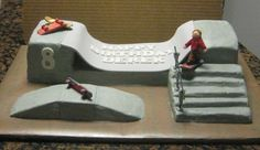"""Skateboard park pieces are all covered in buttercream, with fondant skateboards and boy. Didn't smooth all the buttercream out and kept some of the buttercream """"ruff""""..thought it looked more like cement like that. TFL :)"""