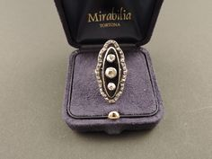 Splendido anello inglese o francese, della fine del XVIII secolo (1790-1800) a forma di marquise, realizzato in oro giallo 18 carati con smalto color blu marino, su cui sono stati incastonati su argento 3 diamanti rotondi, tagliati a rosetta, per un totale di 0,90 punti di carato circa. 33 piccoli diamanti da 0,1 punto di carato circa ognuno, anch'essi montati in argento, fanno da cornice. In vendita su www.mirabilia.gallery per 2.274,00 € (Iva inclusa).