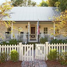 A picket fence and wide front porch give this home old-fashioned charm. Other ways to boost curb appeal: http://www.midwestliving.com/homes/decorating-ideas/curb-appeal/?page=28