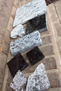 Cambria Praa Sands Quartz, White Ice Granite (left), Kosmus Granite (right), Lennon Granite, Antique Brown (Marron Cohiba) Granite, Bianco Antico Granite