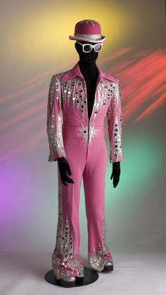 A pink Crimplene jump suit decorated with machine embroidery and mirrors, with matching bowler hat, tinted spectacles and silver platform boots: Designed by Bob Mackie for Elton John, 1972