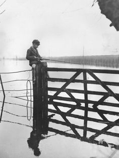 a young boy in his school uniform fishing from a gate near langport, somerset, england, 1935. photographer unknown.