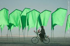 Burning Man girl riding the bicycle in green flag field
