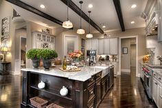 Rustic beams echo the color of dark cabinets in the island, which contrast with white main cabinets. New homes from Toll Brothers. The Enclave at Longview. Waxhaw, NC.