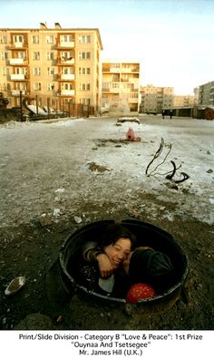"Nikon Photo Contest International 2002-2003 winner: ""Love and Peace (Ouyaa And Tsetsegee)"". In Mongolia's Ulaanbaatar city center, a mother hugs her daughter at the ""front door of her home"". The photographer successfully captured a rare expression of happiness of the ""underground people"", showing their dignity of their lives. Photographer: James W. Hill (UK)."