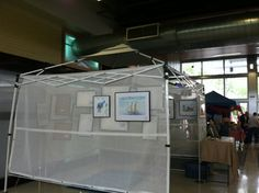 This photo is an artist's booth near mine at a recent event. The mesh screens attached to the tent frame worked great for hanging his watercolors.