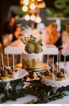 A wedding cake boasting gold foil accents and a topping of indigenous flora, was served with cake pops sporting swirls of chocolate. | Photographer: Lad & Lass | Coordinator: Wedding Concepts | Wedding Cake Baker: Centerpiece Cakes
