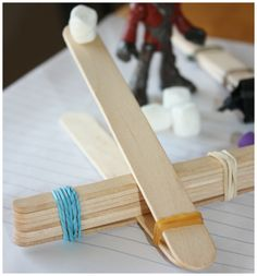 Make a mini catapult with your kids out of popsicle sticks and rubber bands, then measure how far the mini marshmallows fly! Great indoor rainy day activity. #science #math