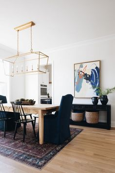 Dining room with dark rug, light wood table, dark chairs and a rectangular lantern chandelier. navy accents are found in the art, vases, chair, and rug. Decorating Your Home, Diy Home Decor, Decorating Ideas, Decor Ideas, Country Wall Mirrors, Oak Floating Shelves, White Couches, The Tile Shop, White Countertops