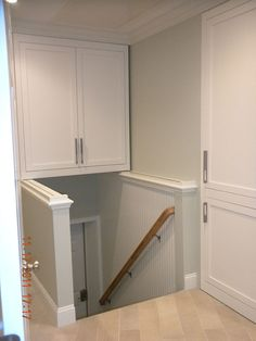 This over stair storage cabinet in Groton, MA is built on rails integrated into the wall caps so that it can be slid forward to access its' contents then slid back out of the way to allow access to stairs