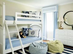 Simple yet Cozy Shared Space - Shades of blue are combined with creams and whites to create a clean, classic color palette for this shared boys room. A mix of patterns, including stripes, graphic and Ikat, add visual interest and texture to the space. Design by Liz Carroll of Liz Carroll Interiors.