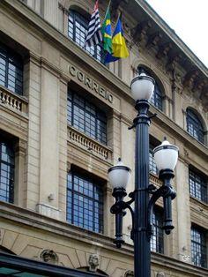 """O edifício dos Correios, inaugurado em outubro de 1922, que funcionou durante muito tempo como sede da empresa em São Paulo (antigo DCT - Departamento de Correios e Telégrafos). O projeto do edifício é de autoria do arquiteto Ramos de Azevedo. Em primeiro plano, um poste modelo 16, na catalogação da """"Light"""", instalados na região central da capital, no final dos anos 20."""
