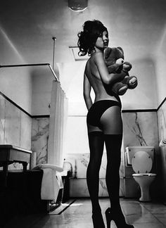 I think this is a fantastic picture at the same time I don't get it. Her shoes are too big, her hair color doesn't work for her, there's a toilet in the background and she's holding a teddybear... Kate Moss, circa 1990-91  Photographer: Kate Garner