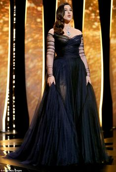 Looking good: Monica commanded attention by virtue of her outfit – a striking semi-sheer black evening gown with a delicately cinched waistline.