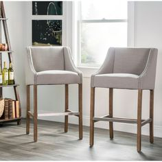 Add modern style to your home decor with this unique Aoki barstool. Constructed with solid, warm wooden legs, this chic bar stool features a French beige upholstered seat with curved arms and bright nailhead accents.