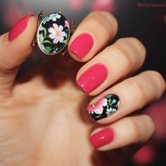 Black Floral Patterned Nail Accent. The artist got the inspiration for this art from a ring that the girl's holding in the picture, but there's nothing wrong with this cheerful nail art design for spring season.