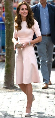 Duchess Kate is wearing a pale pink Lela Rose short sleeve dress, beige wedges, and a gold clutch. The dress is classy and lovely! Kate is wonderful in pink!