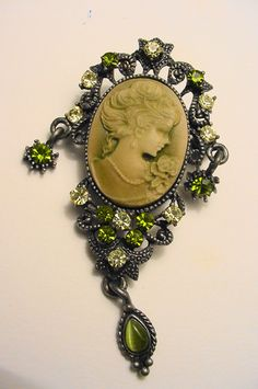 """Gorgeous cameo brooch accented in peridot & citrine Austrian crystal rhinestones, It measures 2 1/2"""" x 1 3/8"""". It has 3 dangles on it, one each side and one at the bottom on a pewter finding.. Color is much more brilliant than this picture."""