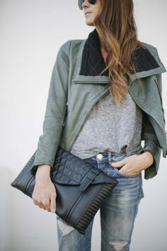 Gray tee, distressed jeans, black ankle booties, green moto jacket, and a black leather clutch
