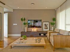 Sala com parede bege + móveis de madeira + tapete de sisal. Projeto e foto Débora Aguiar.