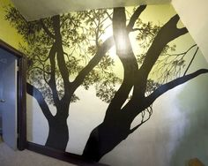 Tree silhouette mural. This demonstrates how a mural can be effective even in a dark, narrow area as in this hallway.