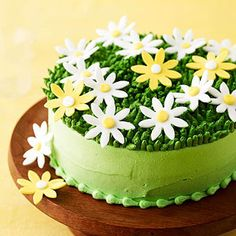 Colored fondant makes the pretty daisies that top this light green frosted cake.