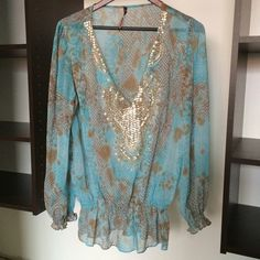 Turquoise Sheer Top Long Sleeve Turquoise Sheer Blouse with gathered waist and sleeves at wrist. Beautiful sequins line the opening! Can be worn as a coverup. Size Small but fits like a Large. Sienna Rose Tops