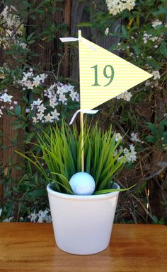 Golf Themed Party Ideas for Father's Day — Here's a simple centerpiece. It's a plant in a pot of grass with a 19th hole flag from Jac o'Murphy. She got her flag from Etsy, but I'm sure there are free printables on the web. #fathersday #partyideas #centerpiece #golftheme