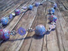 Fröhlich verspielte Kette aus Polymer Clay (Fimo) Perlen.Kleine Blüten in Pudertönen aufgereiht mit kleinen Blümchen aus Fimo und aus Metall, in silbe