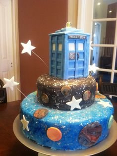 Dr Who Cake - Two Tiered cake with butter cream and fondant icing. Police Box is made of cereal treat and fondant. Lightbulb on top is a Lego.