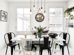 Home tour: un appartement Suédois plein de caractère au charme féminin. Table de cuisine avec suspensions lumineuses.
