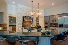 Having designated areas for specific tasks, like an island prep area and cooking alcove, creates an efficient flow in this kitchen. A pair of chandeliers add elegance and anchor the space. The curved island lends itself to effortless entertaining and casual meals at the breakfast bar.