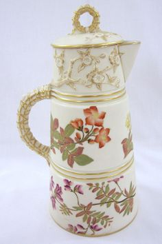 Royal Worcester chocolate pot and cover, floral pattern design with bands of gild around center column and handle. Dated 1884 top/cover replaced in 1988