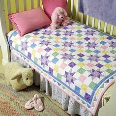 A Star is Born Quilt by Sandra Smith. Pastel prints are perfect for this sweet quilt. The pieced triangles in the border look like prairie points.