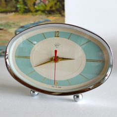 pretty and fresh...perfect bedside clock...    oval chrome trim  front ball chrome feet  cream face with baby blue  gold hands, lines and