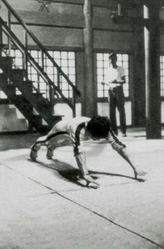 Bruce Lee on set from The Game of Death doing thumb pushups